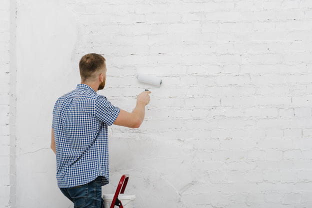 back-view-man-painting-wall_23-2147758685